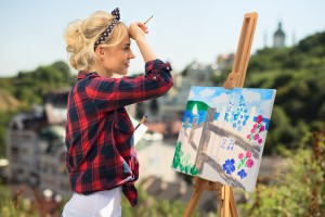 Beautiful blonde woman artist in a playful mood dressed in a plaid shirt. She paints a picture with a brush and paints nature